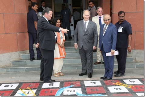 Dr Fisher shows Mawlana Hazar Imam the giant Snakes and Ladders board created as artwork by students and teachers at the Aga Khan Academy, Hyderabad.
