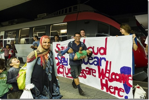 a group welcoming refugees arriving from Syria and Afghanistan at Vienna Railway Station
