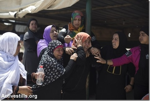 Bedouin women cry as they watch their house being destroyed during the demolition of the unrecognized Bedouin village of Al Arakib
