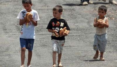 Syrian refugee children carry loaves of bread at a refugee camp in the Turkish border town of Yayladagi, in Hatay province June 27, 2011. REUTERS/Osman Orsal (TURKEY - Tags: POLITICS CIVIL UNREST)