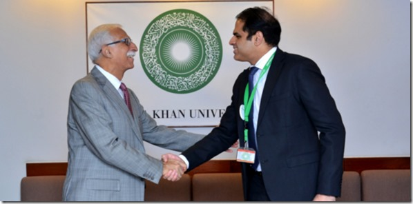 President Firoz Rasul and Dr Babar Hasan shake hands after the gift-signing ceremony