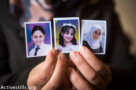 Photos (from left to right) of the killed siblings Mohammed (12), Yara (8) and Nadeen (16) Mahmoud Al Farra, held by their mother in their home in Khan Younis, February 22, 2015. 9 members of the Al Farra family were killed in the street by an Israeli missile while they were fleeing their home after it was attacked on August 1st, 2014.