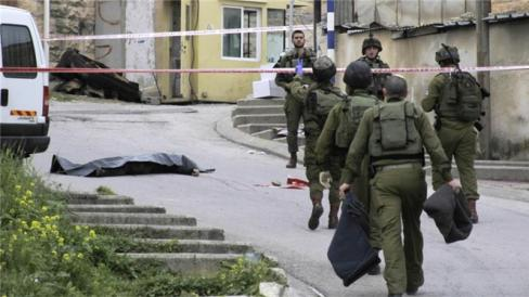 Israeli soldiers stand near the body of Palestinian who was shot while laying wounded on the ground after an alleged attack in Hebron