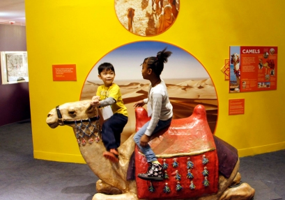 "Children enjoying a ride on a life-size camel in the Trade Routes area of the ""America to Zanzibar: Muslim Cultures Near and Far"" exhibit at the Children's Museum of Manhattan. Photo courtesy of Aoommie Photography"