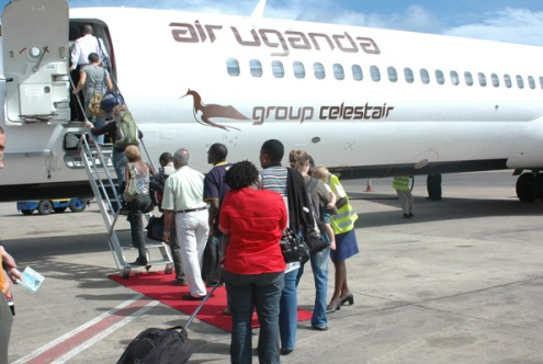Passengers board an Air Uganda aeroplane before it closed. FILE PHOTO