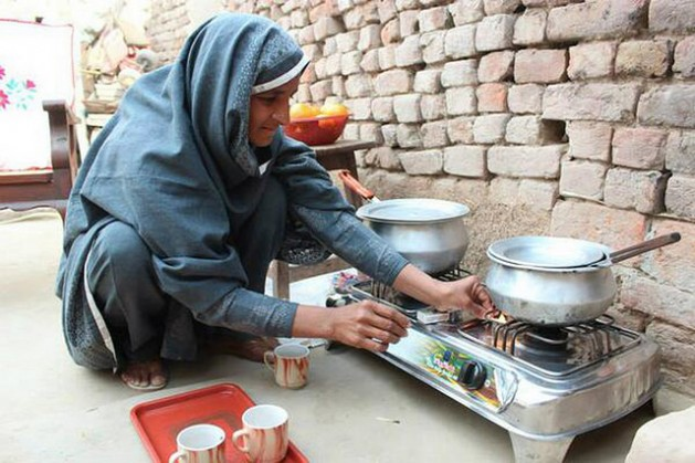 Nabela Zainab prepares tea on the biogas stove in her home in Faisalabad, Pakistan. The stove has eased indoor air pollution and restored her health. Credi- Saleem Shaikh-IPS