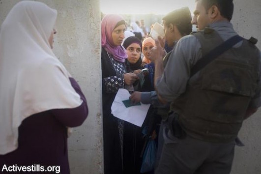 sraeli soldiers check Muslim Palestinian women's IDs as thousands try to pass through the Qalandiya checkpoint on the last Friday during Ramadan,