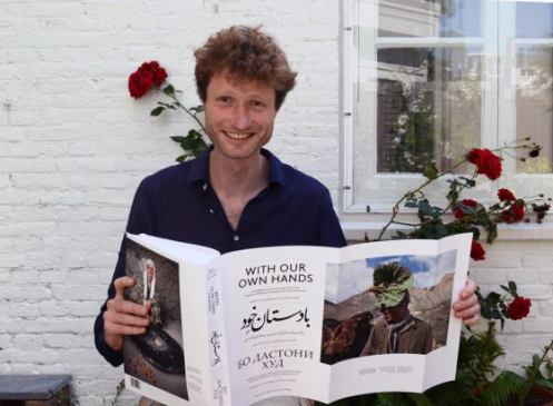 "Frederik van Oudenhoven happily displaying the 688 page book ""With Our Own Hands"" that he co-authored with Jamila Haider."