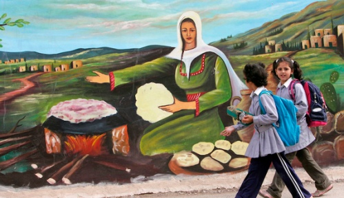 Palestinian schoolgirls walk past a mural painted on a wall in the West Bank city of Jenin November 7, 2007. REUTERS/Mohamad Torokman (WEST BANK) - RTX2BY