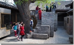 A trail of brick stairs leads up to the roof at the Hutong Children's Library and Art Centre in Beijing, where children delve into the foliage of the big tree