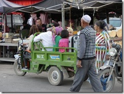 Local transportation at Turpan's buoyant evening market, with people of all ages.
