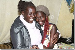 Sheila Jeruto Kipkemboi of University of Eldoret High School in Uasin Gishu County celebrates with a neighbour at their home in Kimumu Estate