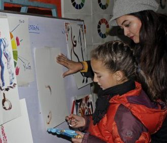 A participant preparing her artwork at the Winter Arts Camp